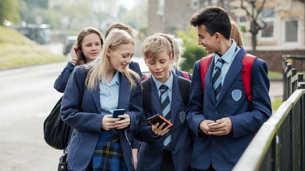 pupils walkes with bags and phones